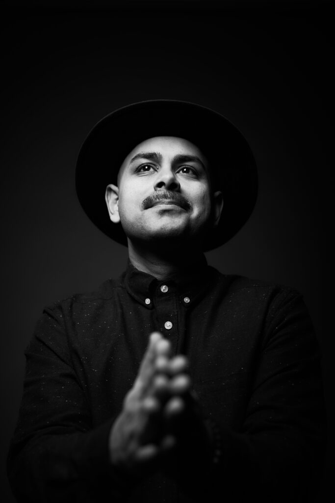 Adil Dhalla wears a wide brimmed hat and looks forward and up as he claps his hands in front of him