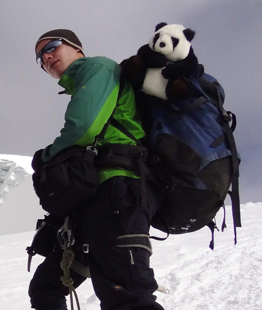 Karim Rikallah is standing on the side of a snow covered mountain wearing a large blue backpack with a plush toy panda attached to it on his back.